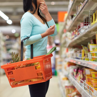 woman holding a hand basket looking at stock on shelves