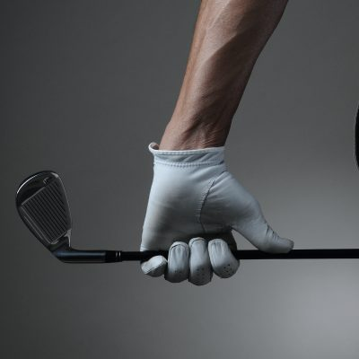 golfer holding a golf club with white golf glove on