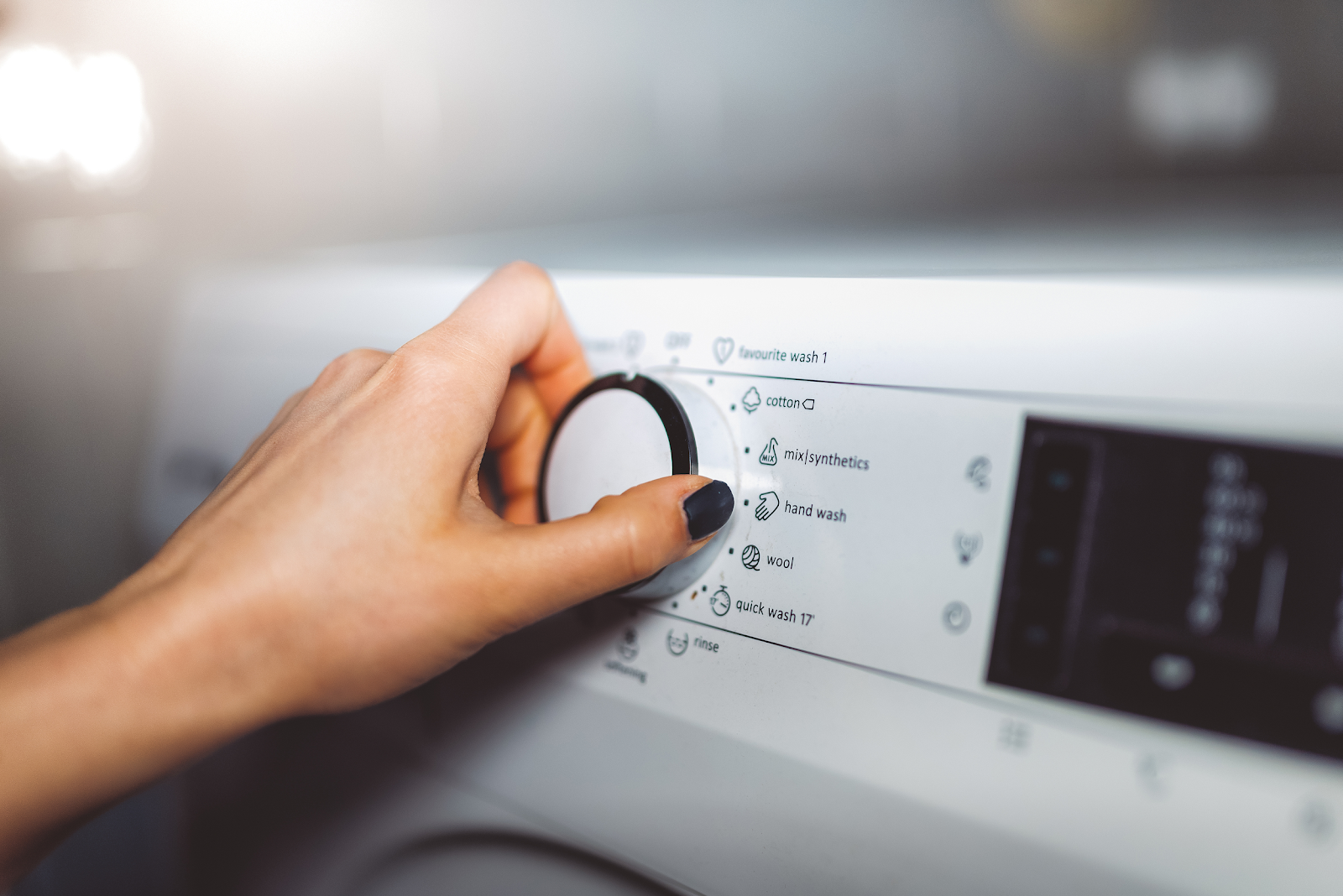 Homeowner adjusting the settings of their washing machine