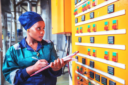 an electricity engineer monitors efficiency in a factory.