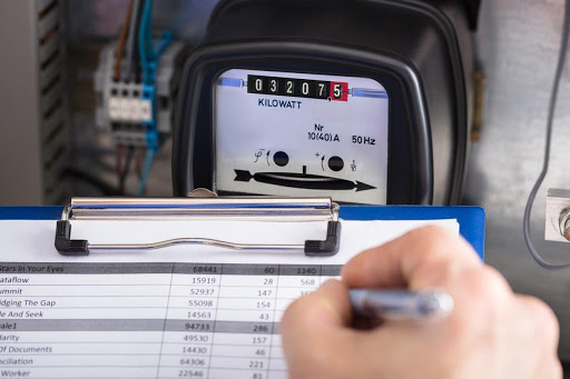 a business employee notes down a kWh reading from an electricity meter.