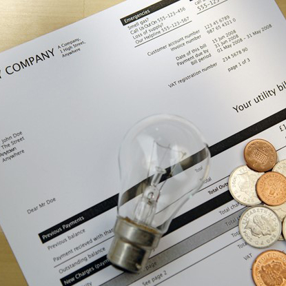 utility bill with coins and lightbulb